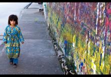 A little girl passing by a wall used by banner makers at small town Hassanabdal. © Awais Yaqub